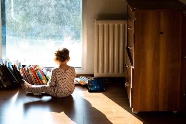 Bambino con pigiama a guardare storie di alcuni bambini nella sua camera da letto.