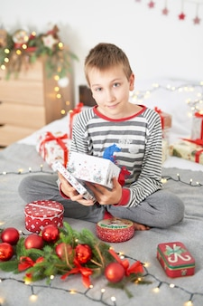Bambino con regali di natale a casa sul letto con decorazioni natalizie