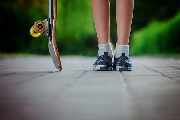 Bambino con skateboard in strada in una giornata di sole