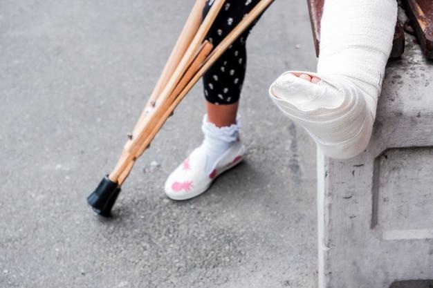 Bambino con stampelle e gambe rotte per camminare, gamba rotta,