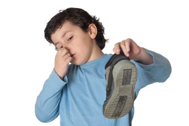 Bambino con un naso chiuso che prende uno stivale isolato su fondo bianco