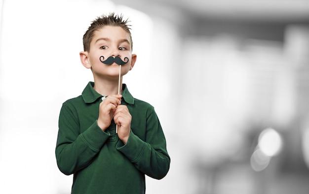 Bambino con un paio di baffi finti