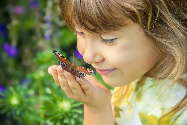 Bambino con una farfalla tra le mani.