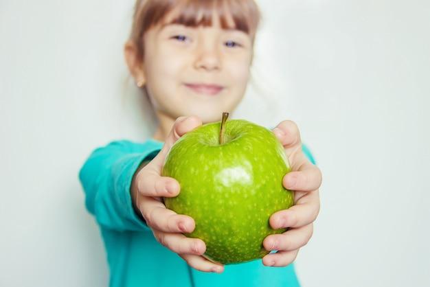 Bambino con una mela. messa a fuoco selettiva natura