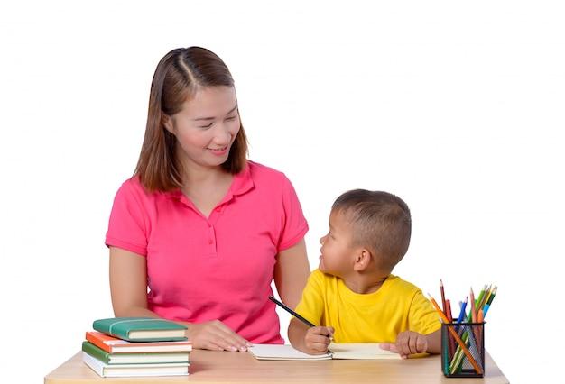 Bambino d'aiuto del giovane insegnante con la lezione di scrittura isolata su bianco