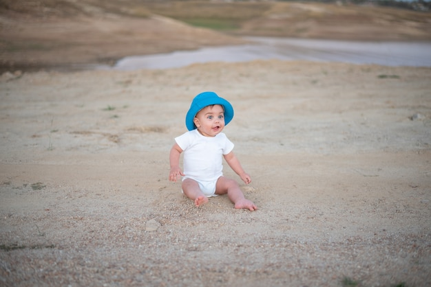 Bambino dagli occhi azzurri con cappello blu seduto sul pavimento di sabbia