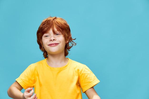 Bambino dai capelli rossi su un blu gesti con le mani