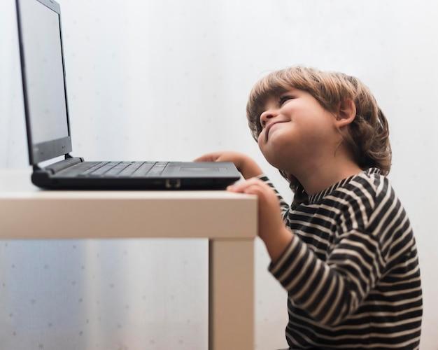 Bambino del colpo medio che esamina computer portatile