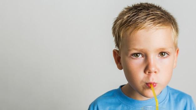 Bambino del primo piano che beve il succo
