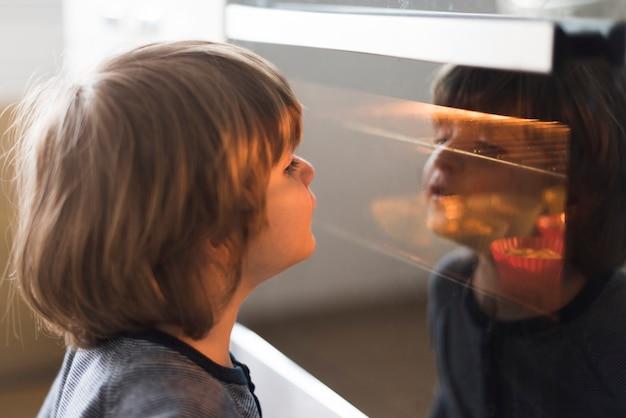 Bambino del primo piano che esamina forno
