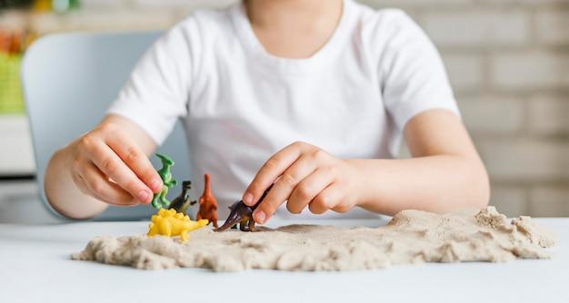 Bambino del primo piano che gioca con i dinosauri