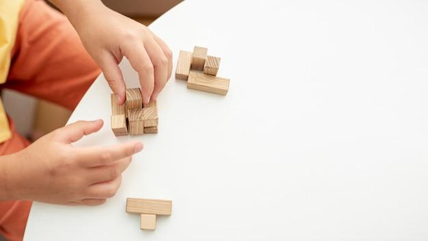 Bambino del primo piano che gioca con i pezzi di jenga