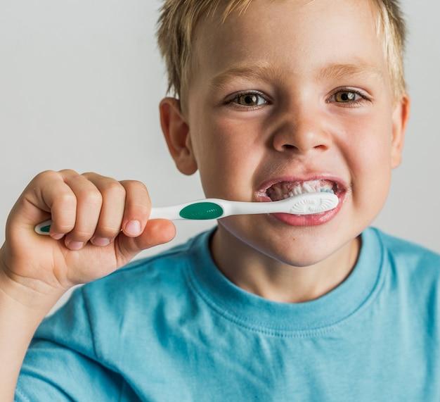 Bambino del primo piano che pulisce i suoi denti
