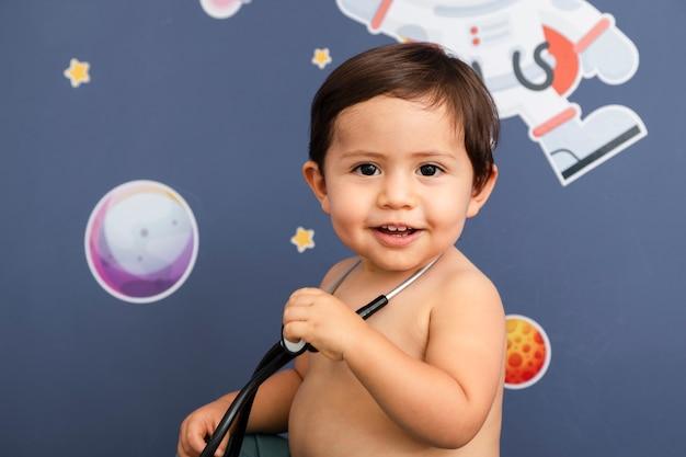 Bambino del primo piano che tiene uno stetoscopio