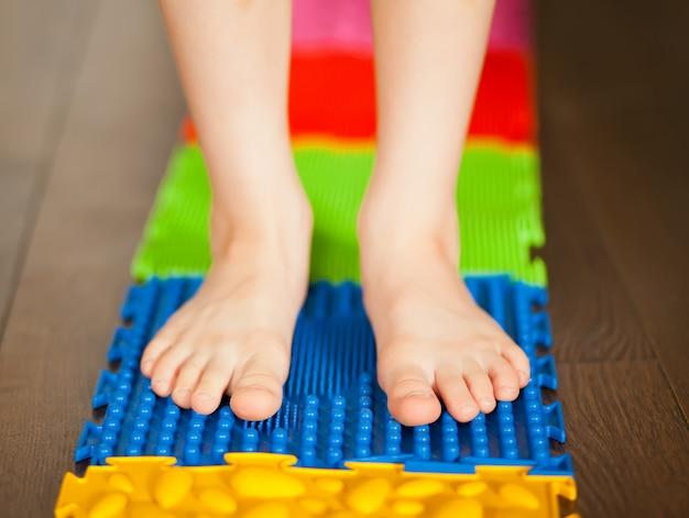 Bambino del ragazzino che cammina su una stuoia ortopedica di massaggio. trattamento e prevenzione dei piedi piatti nei bambini.