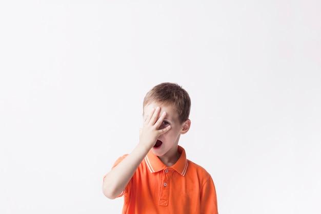 Bambino del ragazzino che dà una occhiata tramite le sue dita che stanno sul contesto bianco