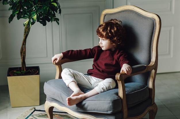 Bambino del ragazzo in abbigliamento casual che posa nella poltrona