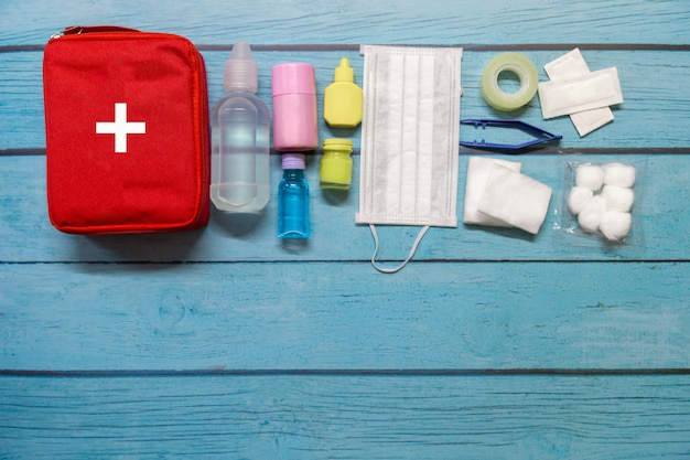 Bambino del sacchetto del pronto soccorso di vista superiore con i rifornimenti medici su fondo di legno.