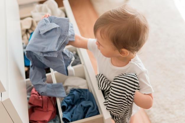 Bambino dell'angolo alto che prende i vestiti dal cassetto