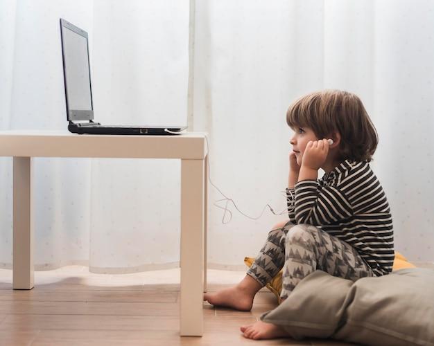 Bambino della foto a figura intera che esamina computer portatile