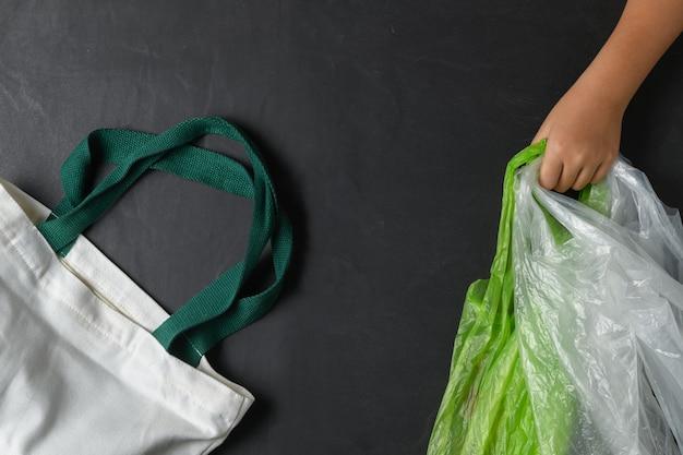 Bambino della mano che tiene i sacchetti di plastica