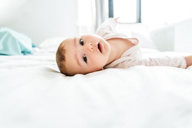 Bambino di 6 mesi che esamina macchina fotografica di mattina che si trova sul letto fra gli strati bianchi