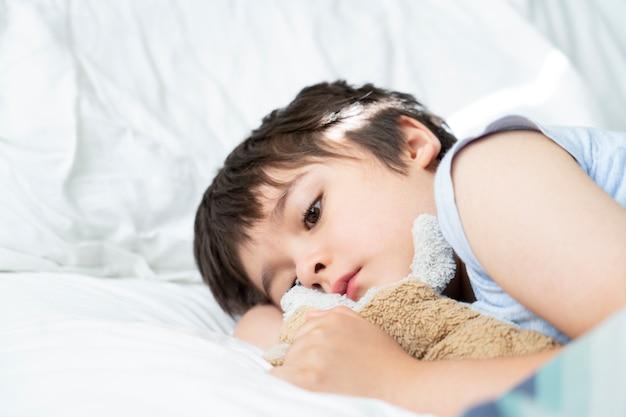 Bambino di 7 anni sdraiato sul letto, bambino assonnato che sveglia la mattina nella sua camera da letto con la luce del mattino