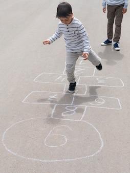 Bambino di alta vista che gioca a campana con suo fratello