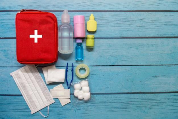 Bambino di borsa di pronto soccorso vista dall'alto con forniture mediche su legno