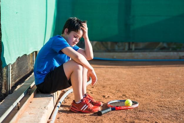 Bambino di lato seduto dopo la partita