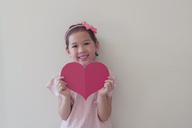 Bambino di razza mista che tiene un grande cuore rosso, salute del cuore, donazione, carità volontaria felice, responsabilità sociale, giornata mondiale del cuore, giornata mondiale della salute, giornata mondiale della salute mentale, benessere, concetto di speranza