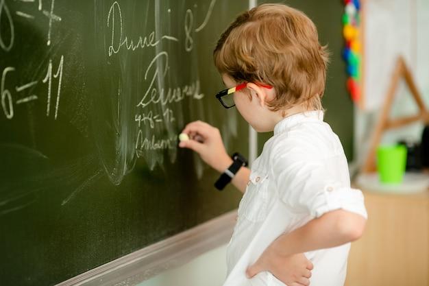 Bambino di sette anni con gli occhiali a scrivere i compiti a scuola. ragazzo studiando al tavolo su sfondo di classe