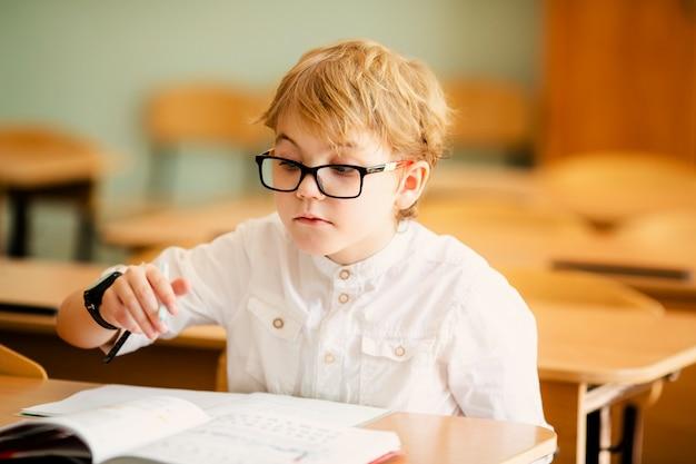 Bambino di sette anni con gli occhiali a scrivere i compiti a scuola