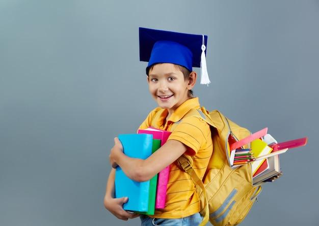 Bambino di successo con tappo di laurea e zaino pieno di libri