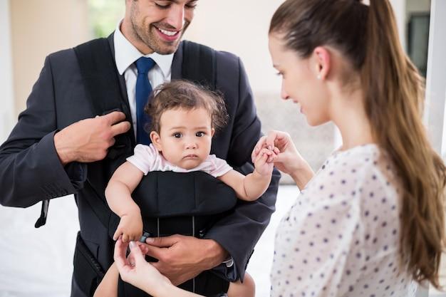 Bambino di trasporto sorridente del padre con la madre