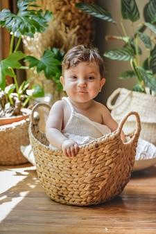Bambino di un anno che sorride e che posa dentro un canestro