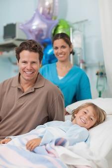 Bambino disteso su un letto medico accanto a suo padre