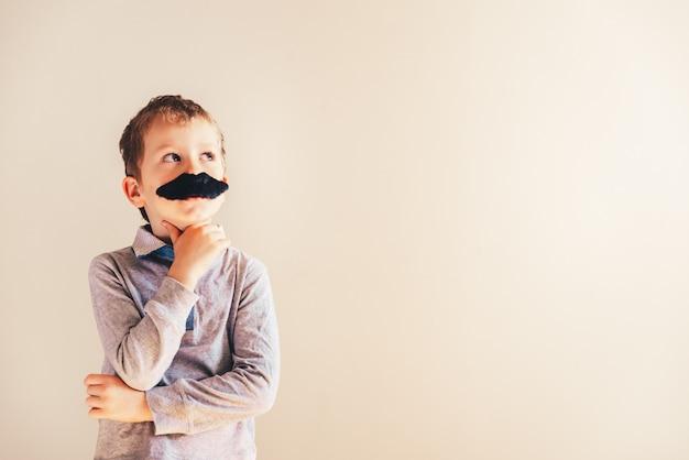 Bambino divertente con baffi finti gesticolano come un uomo adulto, la maturità e il concetto di business.