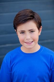 Bambino divertente con dieci anni con t-shirt blu