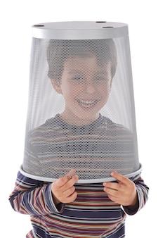 Bambino divertente con la spazzatura in testa su uno sfondo bianco