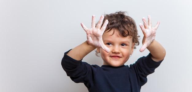 Bambino divertente e gioioso mostra i suoi palmi insaponati