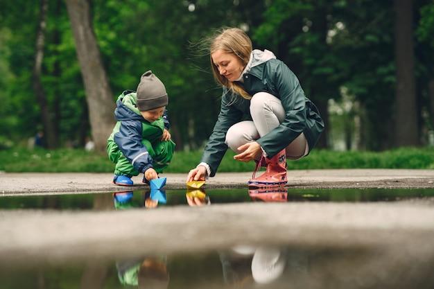Bambino divertente in stivali da pioggia che giocano in un parco di pioggia