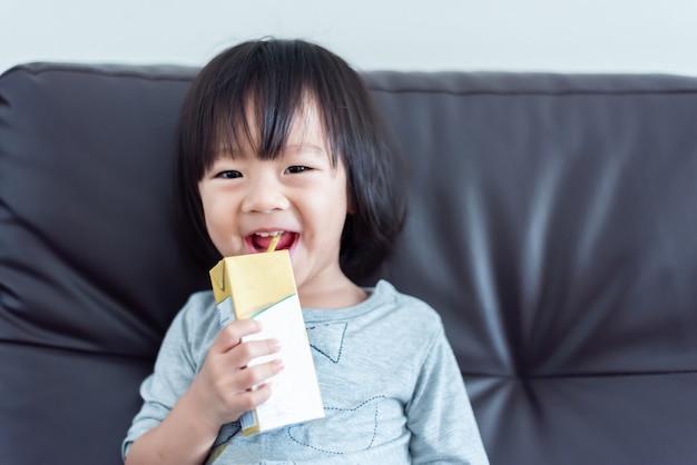 Bambino dolce asiatico felice del bambino che beve un cartone di latte dalla scatola