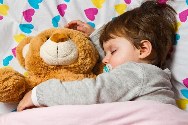 Bambino dolce che dorme con l'orsacchiotto