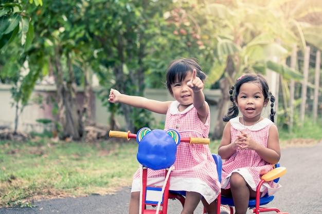 Bambino due bambine che cercano qualcosa e divertirsi per girare il triciclo