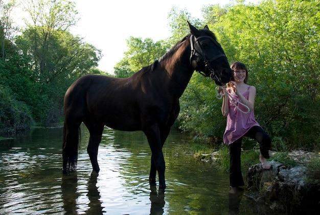 Bambino e cavallo nel fiume