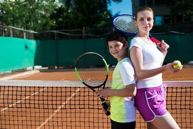 Bambino e donna schiena contro schiena sul campo da tennis