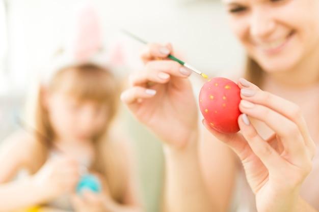 Bambino e madre che dipingono le uova di pasqua