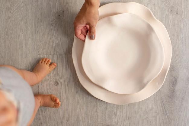 Bambino e mamma con piatti di ceramica bianchi su fondo di legno