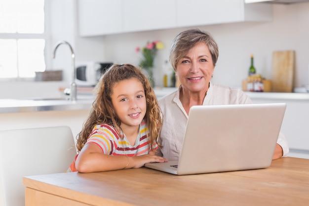 Bambino e nonna guardando la telecamera con il portatile